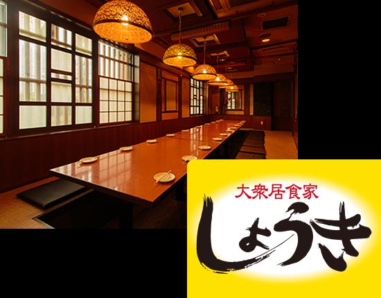 画像:大衆居食家しょうきの店内の様子。奥行きがある店内で、木目調の店内に、暖かい光でライトアップされています。テーブルには、お皿とお箸が並べられています。