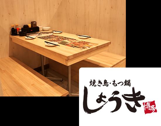 画像:木目調の店内でテーブルも木のテーブル。テーブルには、4人分のお箸をお皿が用意されており、中央にはメニュー。テーブルの端にはソースや小皿が用意されています。