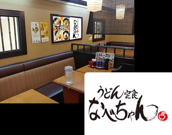 画像:うどん定食なべちゃんの店内、濃い茶色の窓枠があり、竹の仕切りが窓にいくつもついています。店内の壁には、ビールのポスターや、人気のうどんメニューのポスターが貼っています。4人ほど座れるテーブルがいくつもあり、テーブルの上にはお水、テーブルの端にはメニューや調味料が用意されています。