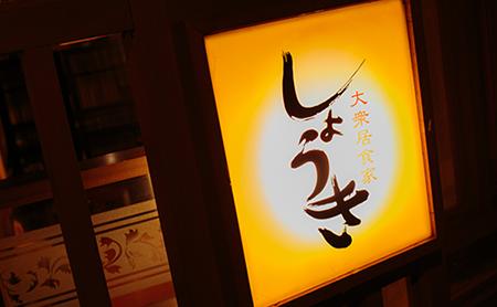 画像:お店の外、ライトで明るく光る、大衆居食家しょうきの看板。