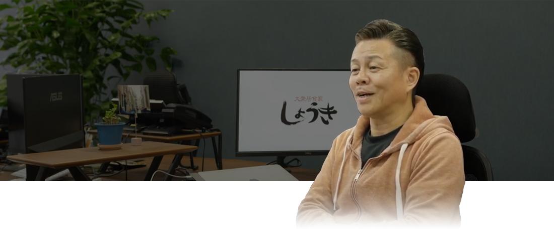 画像:トップメッセージ。パソコンの前に座り、えみを浮かべる 株式会社しょうき企画 代表取締役 渡邉 司