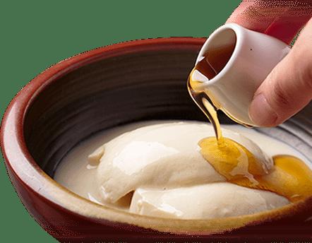 画像:お豆腐が茶色で丸みの器に入っていて、お豆腐にタレをかけている様子。