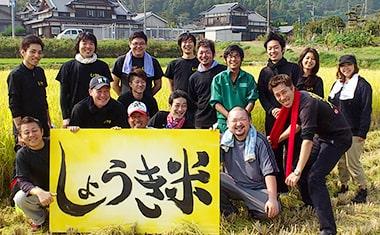 写真: 畑の前で、しょうき関係者や農家さんと一緒に記念撮影をしている様子。