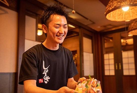 写真:店内で、黒のスタッツTシャツをきた男性スタッフが笑顔で刺身盛りを提供している様子。